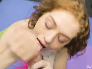 Redhead chick with curls sucks dick in the gym