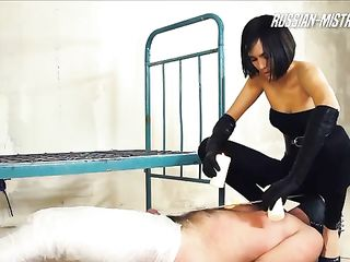 Mistress pours melted wax on testicles of bound man