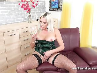 Woman in a green corset drinks urine from a glass