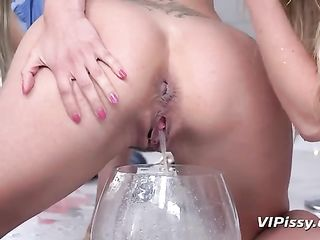Two blondes pour urine and kiss passionately