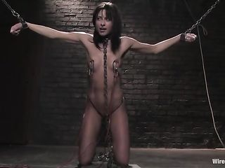 A woman hanging on chains is tormented by a naked Mistress