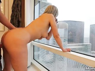 MILF bends down by the window while she is fucked by a young lover