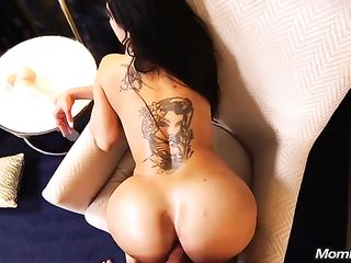 Brunette with a tattoo on her back spreads her buttocks and gives a fuck in the ass