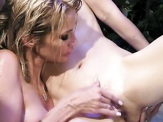 Jessica Drake and Charlotte Stokely caress each other's wet bodies in the pool