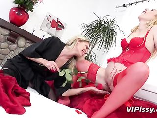 The girl in silk robe touches blonde's pussy in red corset with a rose