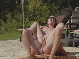 Redhead in sunglasses is having sex by the pool