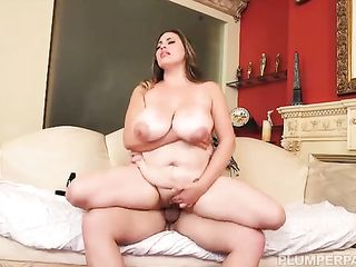 Fat woman has sex on the sofa by the fireplace