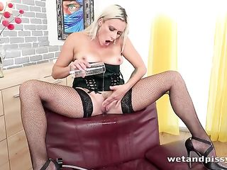 Woman in a corset pumps her labia with pump and pissing