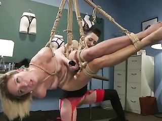 The girl pokes a stick in the pussy of the blonde tied to the ceiling