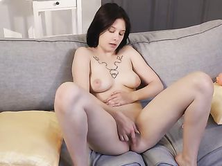 The girl with a tattoo over her chest caresses her pussy with her hand
