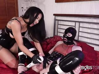 Transsexual in a leather mask makes brunette play with his penis