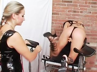 Woman in a latex costume puts clothespins on another woman's pussy and douses her body with molten wax