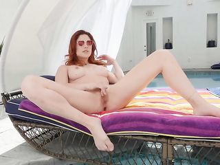 Molly Stewart fondles her shaved pussy by the poollly Stewart