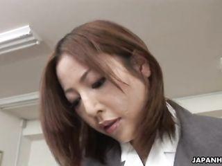 Emiri Mizukawa in uniform sits on a transparent phallus on an office desk