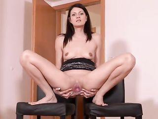 Tiny Tina shows her pussy between two chairs