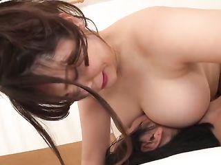 Young man kissing Japanese masseuse's tits