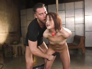 Fucks a girl tied to the ceiling in the mouth