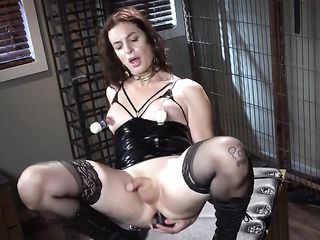 A gagged transsexual fucks himself in the ass with a black phallus