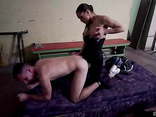 Mistress in a corset has her slave in different positions with a strap-on