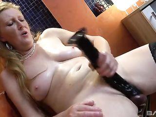 Older woman in stockings pleasures herself with huge artificial dick