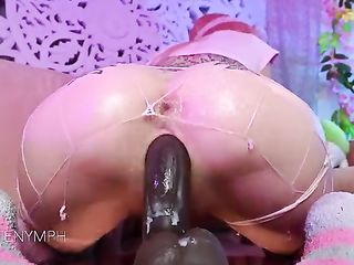 Pretty girl with a tattoo on her butt sits down on a silicone dildo