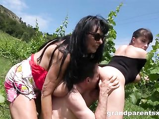 Dude fucks two older ladies in the bushes